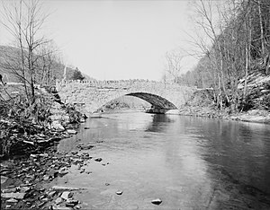 Black and white photograph of a cracked stone bridge partly reflected in a stream. Both of the stream banks are wooded.