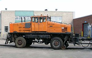"""Heavy work trains are hauled with sizeable tractors such as this old (1966) """"Duplex"""". Traction is effected through the rubber-tired wheels, and guidance through the retractable flanged wheel. This tractor can also operate on the road."""