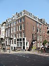 foto van Hoekhuis, onderdeel van oud huizenblok met doorlopend dwars dak. Voor- en zijgevels onder omlopende rechte lijst