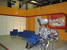 Orange, red and white TV studio, with blue chairs and gray camera