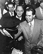 A smiling young man shakes hands; a Nixon bumper sticker is seen.
