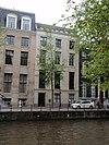 foto van Pand met zandstenen gevel van uitzonderlijk ontwerp, met panelen op de brede vensterdammen, guirlandes en een geblokte onderpui onder rechte lijst