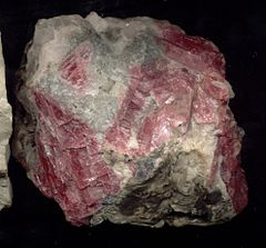 A rough chunk of rhodonite showing white and intense pink crystals.