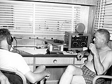 This is a photo of Dr. Walter F. Mazzone and Dr. George Bond inside the communications center of SEALAB I