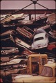 STACKED AUTOS ARE CRUSHED AND SHIPPED TO JAPAN, THEN RETURN TO THE UNITED STATES AS TOYOTAS AND DATSUNS TO BEGIN THE... - NARA - 555492.tif