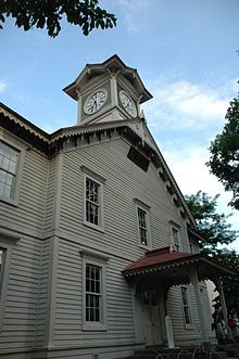 Photograph of a white wooden building against a blue sky.  The building is of Western architectural design built with subtle Japanese details.  A clock tower rising from the front of the building is the dominant feature.