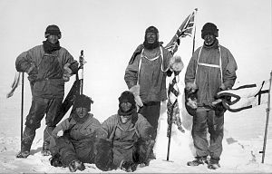 Five men in heavy clothing and headgear; three are standing and two seated on the ground. The standing men carry flags; all five have dejected expressions