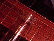 A bottleneck slide on an acoustic guitar