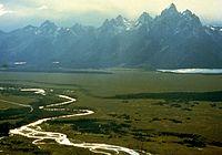Ein geflochtener heller Bach schlängelt sich links unten über ein flaches, grasbewachsenes Tal, während sich gezackte graue Gipfel mit Schneestreifen unter einem hellen Himmel über einem fernen See erheben