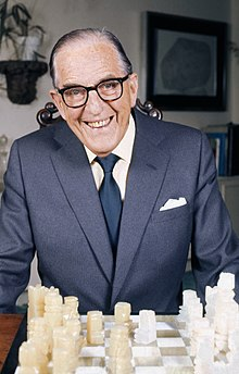 An elderly man sitting at a chess board wearing glasses smiling broadly at the camera