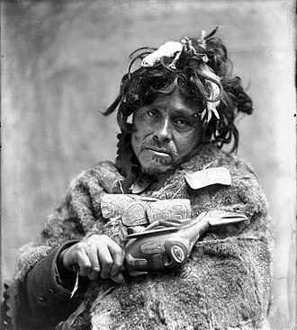 Angoon bombardment - Tlingit Shaman, ca. 1900. Portrait of man wearing fur cape and carved amulet necklace, holding raven rattle