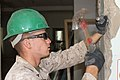 U.S. Marine Corps Lance Cpl. Ryan E. Brake, with the 9th Engineer Support Battalion, 3rd Marine Logistics Group, III Marine Expeditionary Force, breaks off chunks of an inner wall to make room for a door frame 130726-M-DR618-045.jpg