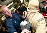 U.S. Navy Electronics Technician 3rd Class Michael Pavlik helps Electronics Technician 2nd Class Roberto Perry put on a full firefighting ensemble as part of damage control olympics aboard the guided missile 120125-N-OH194-285.jpg