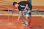 U.S. Navy Logistics Specialist 2nd Class Yanbin Kuang, assigned to the guided missile destroyer USS Higgins (DDG 76), hoses down a pool deck during a community relations event at the Bahrain Mobility 130617-N-UP025-003.jpg