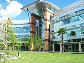 A modern építészeti stílusú épületet kő, fém és üveg borítja a fák és a kék ég hátterében.