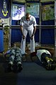 US Navy 050530-N-5637H-003 Naval Reservist, Master-at-Arms 2nd Class David Coleman, instructs two young kids as they perform push-ups for posters at the Navy Recruiting District New York display.jpg