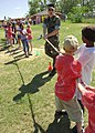 US Navy 060512-N-6889J-017 Religious Program Specialist 3rd Class Joseph Ditzel assists children in a game of tug-o-war at Harrison Central Elementary School in Gulfport.jpg