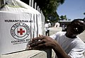 US Navy 100125-N-6266K-238 A Red Cross worker picks up a humanitarian box to give to an earthquake survivor in Port-au-Prince.jpg