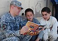 US Navy 101003-N-7062A-001 Lt. Matthew Marcinkiewicz practices reading English with children of soldiers from the Afghan National Army.jpg