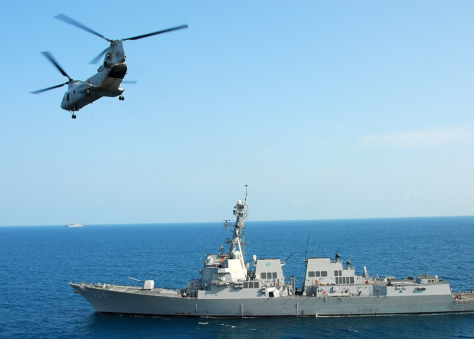 US Navy 110217-N-8607R-204 A CH-46E Sea Knight helicopter flies by the guided-missile destroyer USS Stockdale (DDG 106)