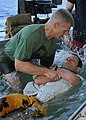 US Navy 110306-N-YB753-054 Cmdr. Thomas Webber submerges Cmdr. John DeBellis in water during a Protestant baptism at sea aboard USS Abraham Lincoln.jpg