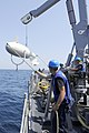 US Navy 110723-N-WL435-036 Sailors aboard USS Gladiator (MCM 11) maintain positive control of a mine sweeping floatation device as it is craned abo.jpg