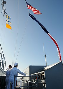 US Navy 120123-N-BK435-007 Sailors assigned to the submarine tender USS Frank Cable (AS 40) raise the Ensign and the 165-foot Homeward Bound Pennan.jpg