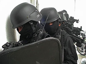Special police - Malaysian PGK A operatives moving crosshairs during the Close Quarters Combat drill at the killing house before raid. The first operative is equipped with Tactical Shield. Taken at the PGK A Special Operations Killing House in Bukit Aman, Kuala Lumpur.