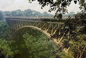 An impressive steel railway bridge above a wide tree-lined gorge.