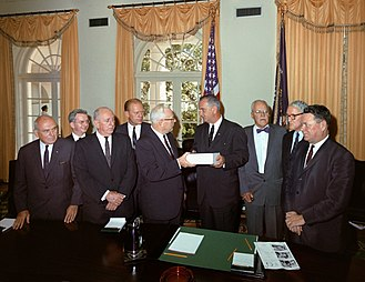 Warren Commission - The Warren Commission presents its report to President Johnson. From left to right: John McCloy, J. Lee Rankin (General Counsel), Senator Richard Russell, Congressman Gerald Ford, Chief Justice Earl Warren, President Lyndon B. Johnson, Allen Dulles, Senator John Sherman Cooper, and Congressman Hale Boggs.