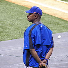 An African-American man, wearing a baseball hat and jacket, stands outside a baseball diamond.