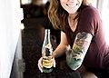 Woman with tattoo drinking (Unsplash).jpg