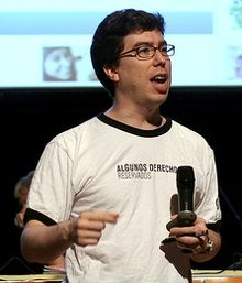 waist high portrait wearing a T-shirt and holding a microphone