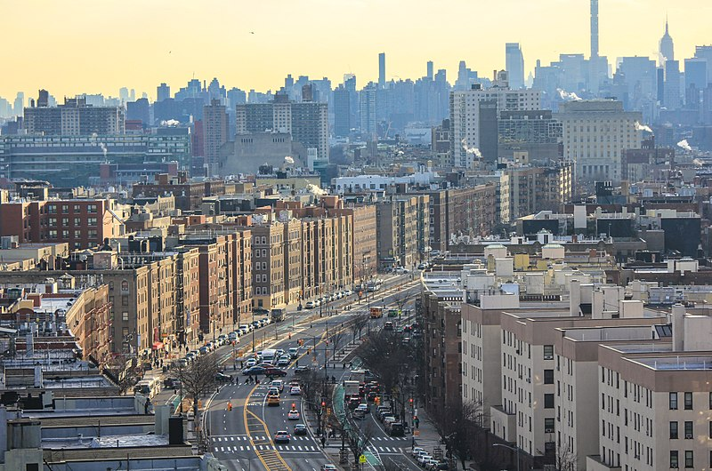 View in February 2018 of the Grand Concourse in The Bronx, foreground, with the Manhattan skyline in the background.