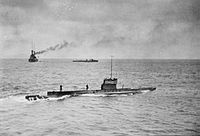 A submarine sailing on the surface of the ocean, while in the background is a large warship and a smaller vessel