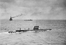 A submarine sailing on the surface of the ocean, while in the background is a large warship and a smaller vessel.
