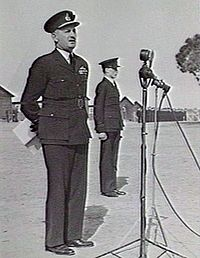 Man in dark military uniform with peaked cap in front of microphone