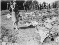 A German girl is overcome as she walks past the exhumed bodies of some of the 800 slave workers murdered by SS guards... - NARA - 531343.tif