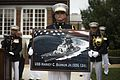 A Marine holds a poster of the future Arleigh Burke-class guided-missile destroyer USS Harvey C. Barnum, Jr. (28019391344).jpg