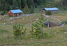 Two log cabins with metal roofs in the distance down a rolling slope. The remains of another are partially visible closer to the camera