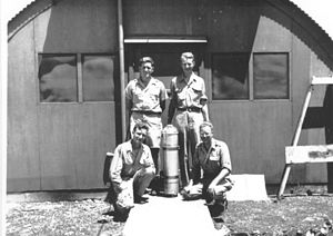 Project Alberta - Project Alberta's Harold Agnew (top left), Luis Alvarez (top right), Lawrence Johnston (bottom left) and Bernard Waldman (bottom right) in front of the instrumentation laboratory on Tinian with a Bangometer canister. These were dropped by parachute to measure the force of the blast.