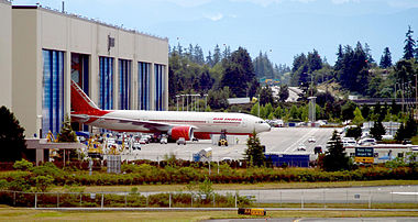 Aircraft factory. Rectangular building with six doors, one of which is open to reveal an emerging airliner. The background is a forest; small vehicles and taxiways surround the factory.