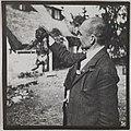 Akseli Gallen-Kallela holding a puppy in his hand at Tarvaspää, 1914. (14725751071).jpg