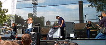 Annie, a drummer, and a keyboardist performing to a crowd at an outdoor festival.