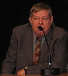 Color photo: Medium shot of Arto Paasilinna, sitting behind a table, speaking into a microphone