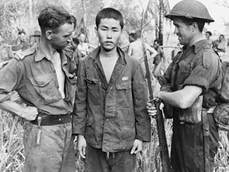 Japanese prisoners of war in World War II - Two Australian soldiers with a Japanese POW in October 1943.