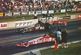Kenny Bernstein - Bernstein (red dragster in near lane) reversing back to the start line after a burnout. Larry Dixon is opposite Bernstein.