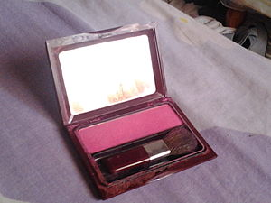Rouge (cosmetics) - A rouge compact containing a mirror and brush