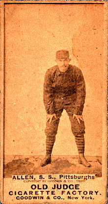 An unclear baseball card image of a mustachioed man in a dark baseball uniform and matching cap crouching with his hands on his knees