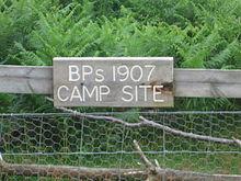 """cartello in legno su una recinzione, leggendo """"BP's 1907 CAMP SITE"""""""